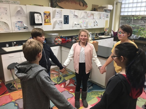 Six young people are holding hands in a circle in a colorful science classroom.