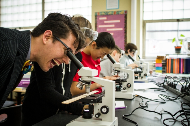 A man smiles while looking into a microscope next to several students in a science lab.